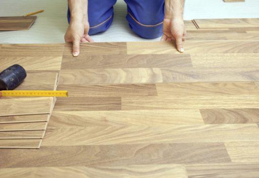 Carpenter installing wooden floor - home improvement